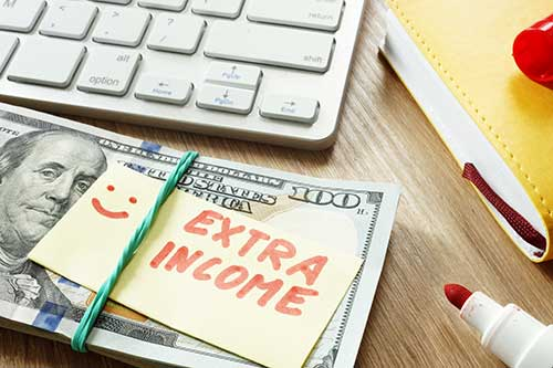 Cash with notepad on top with extra income written on top